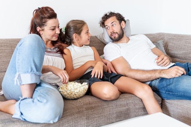 Familia comiendo palomitas de maíz en el sofá