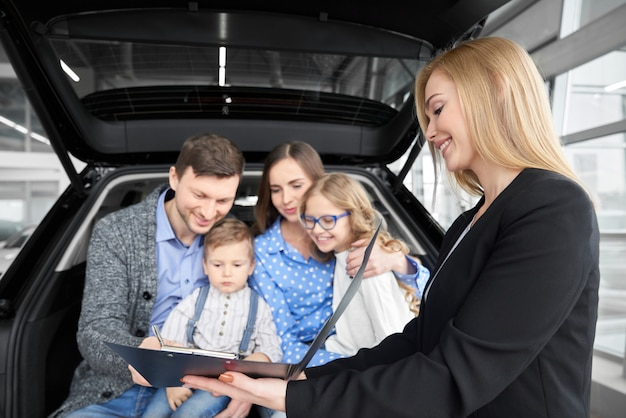 Familia compra automóvil, hombre firma documento de compra.