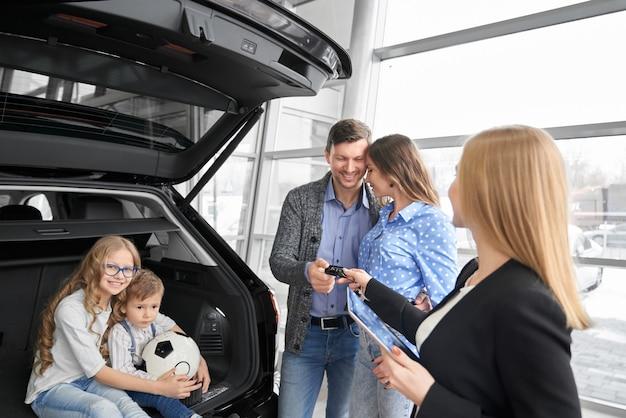 Familia comprando auto en concesionario, gerente dando las llaves del auto.