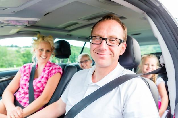 Familia conduciendo en coche con cinturón de seguridad abrochado.