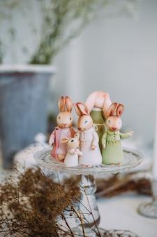 Familia de conejos de juguete en una bandeja de vidrio entre la decoración y las plantas. concepto de vacaciones familiares de pascua.