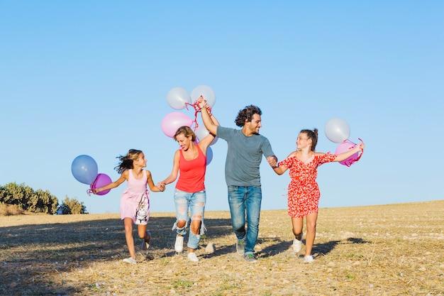 Familia corriendo en campo y sosteniendo globos
