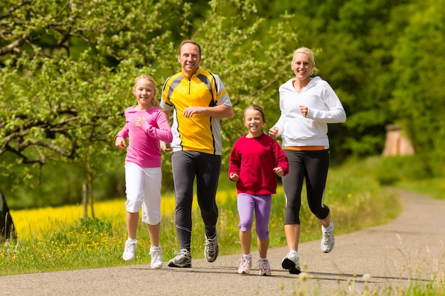 Familia corriendo en el prado por deporte