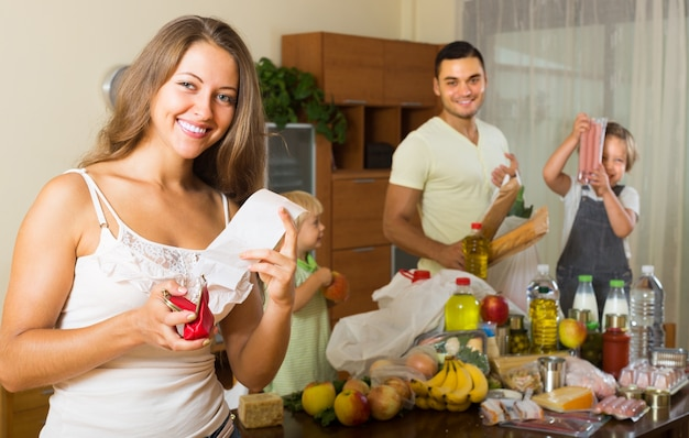 Familia de cuatro con bolsas de comida