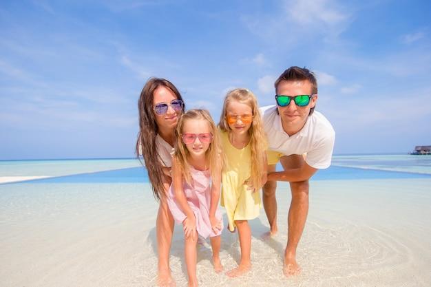 Familia de cuatro jóvenes en vacaciones en la playa. de cerca