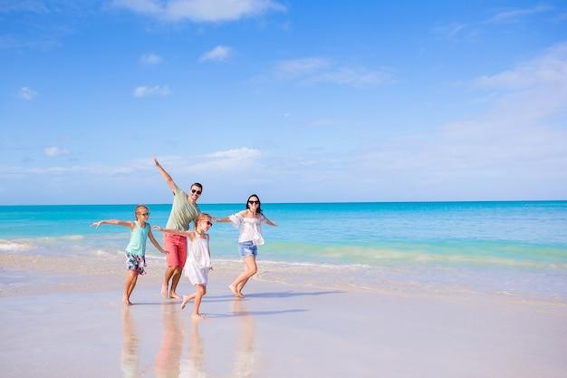 Familia de cuatro en vacaciones en la playa corriendo y divirtiéndose