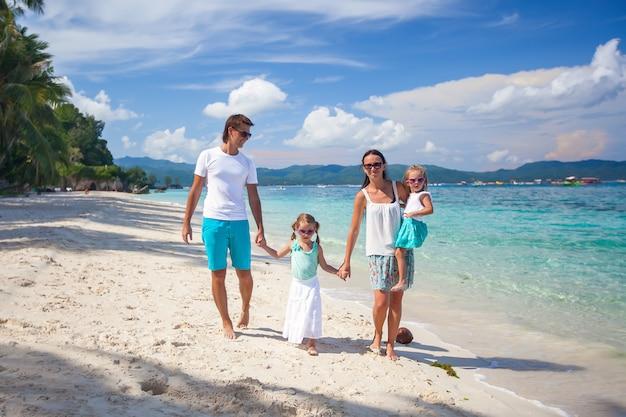 Familia de cuatro en vacaciones en la playa