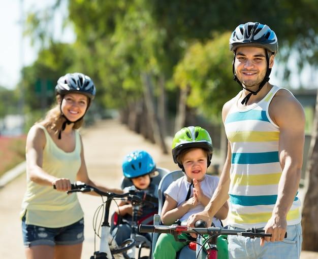 Familia de cuatro personas en bicicleta en la calle