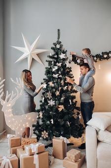 Familia decorando el árbol de navidad juntos. árbol de navidad.