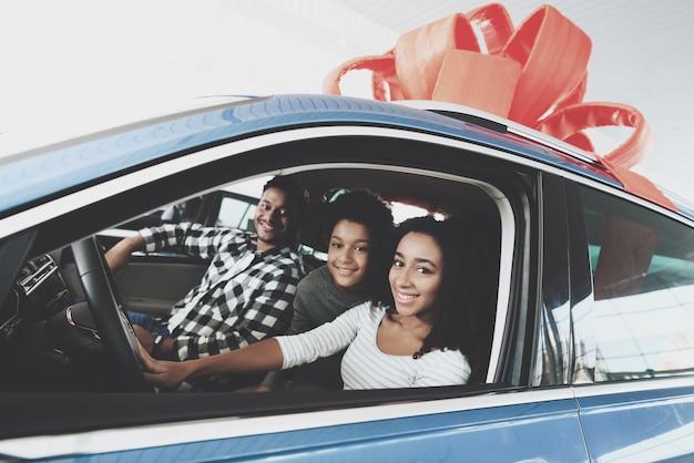 Familia dentro de coche nuevo con concepto de regalo de lazo rojo