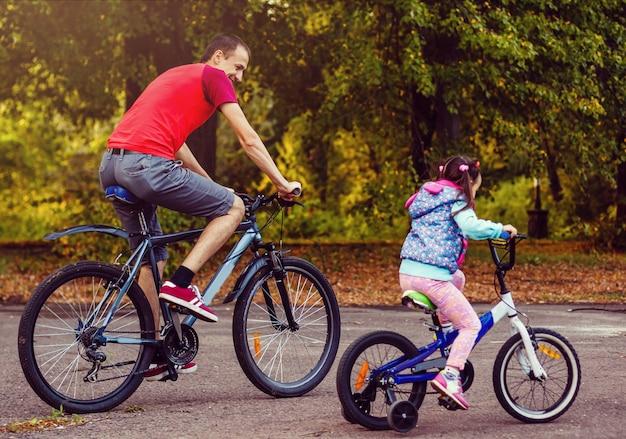 Familia deporte padre e hija montando bicicletas en bosque verde