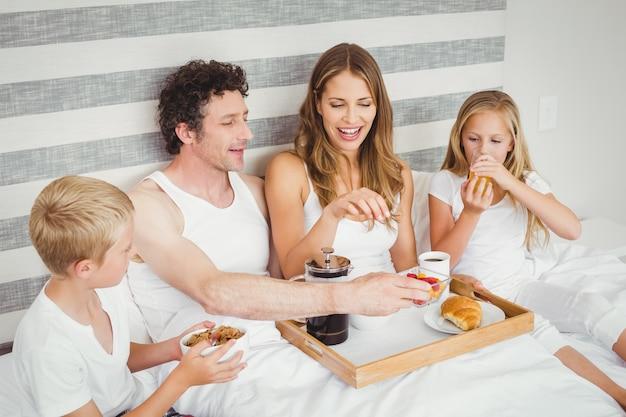 Familia desayunando en la cama