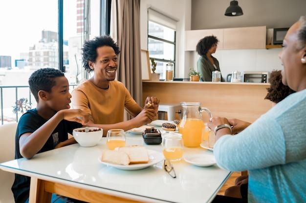 Familia desayunando juntos en casa.