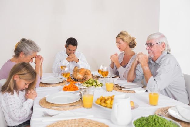 Familia diciendo gracia antes de comer un pavo