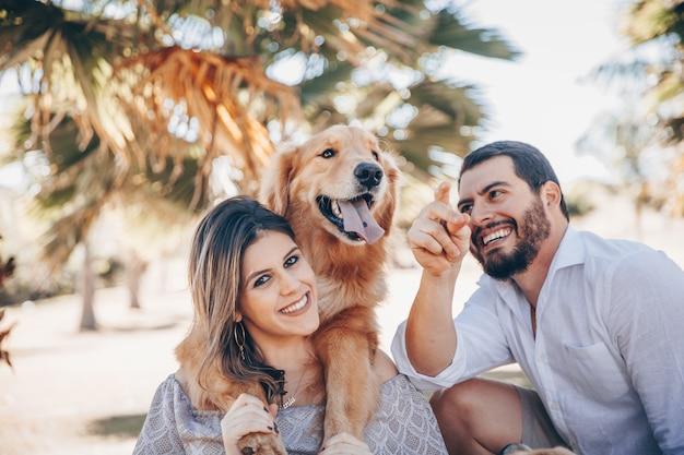 Familia disfrutando de un día soleado en el parque con su mascota.