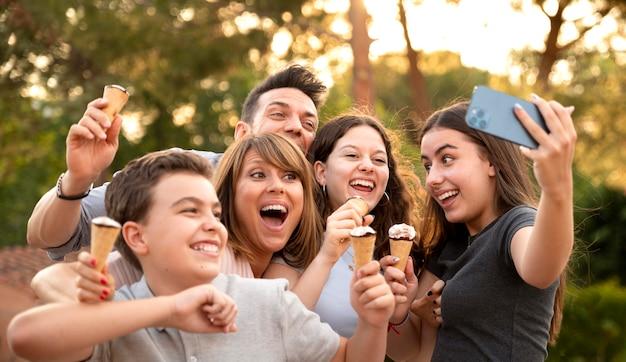 Familia disfrutando de un helado juntos al aire libre y tomando selfie