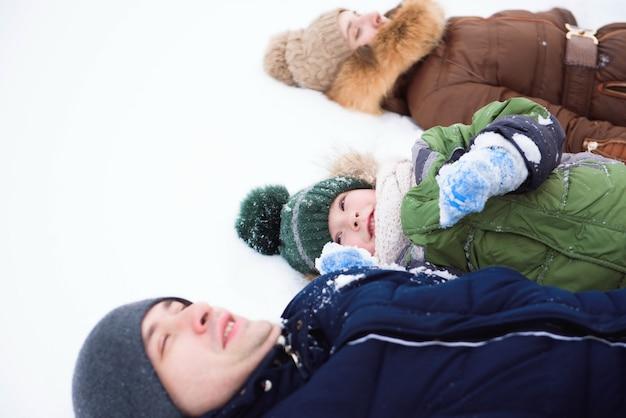 Familia divirtiéndose, jugando en el paseo de invierno al aire libre
