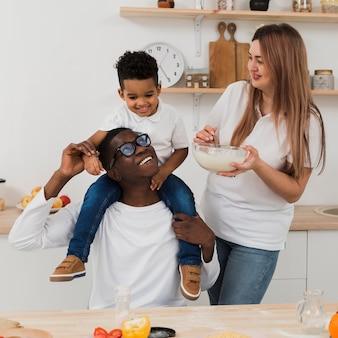 Familia divirtiéndose mientras prepara algo de comida en la cocina