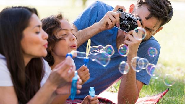 Familia divirtiéndose en el parque mientras sopla burbujas