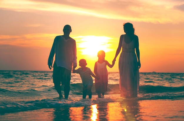 Familia divirtiéndose en vacaciones con perfecta puesta de sol