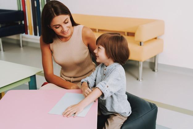 Familia en doctores en sala de espera que el niño dibuja con mamá