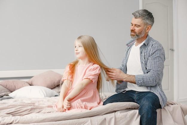 Familia de dos generaciones. hombre maduro cepillando el cabello de la niña. adorable.
