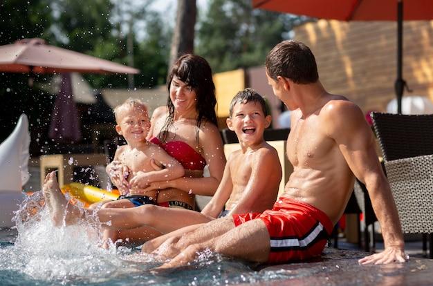 Familia con dos niños disfrutando de su día en la piscina.