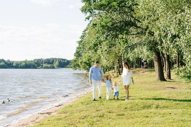 Una familia con dos niños pequeños camina a lo largo de la orilla del lago en el verano