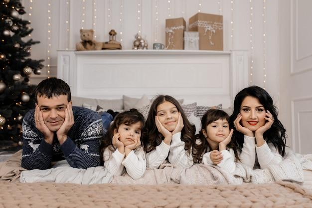 Familia encantadora de pareja agradable con tres niños encantadores en b
