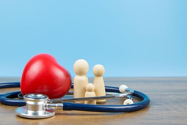 Familia con estetoscopio y un corazón rojo. conceptos de examen físico y seguro de salud.