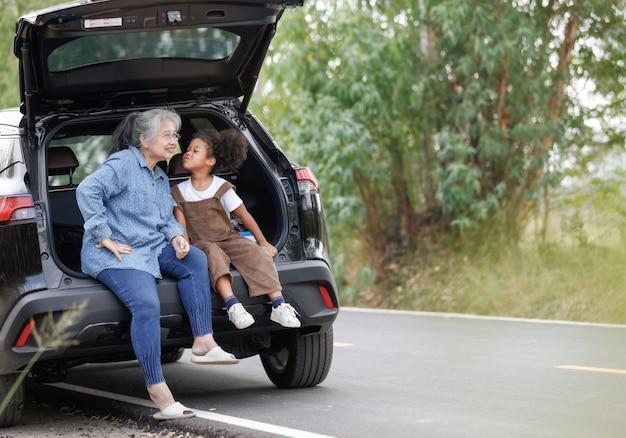 La familia étnica muestra amor juntos en la parte trasera del automóvil durante el viaje por carretera