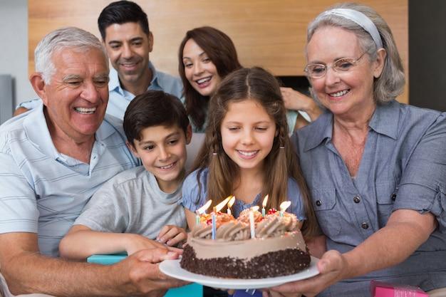 Familia extendida con torta en la sala de estar
