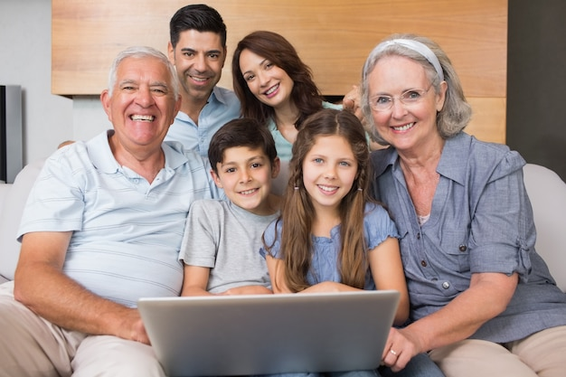 Familia extendida, usar la computadora portátil, en, sofá, en, sala