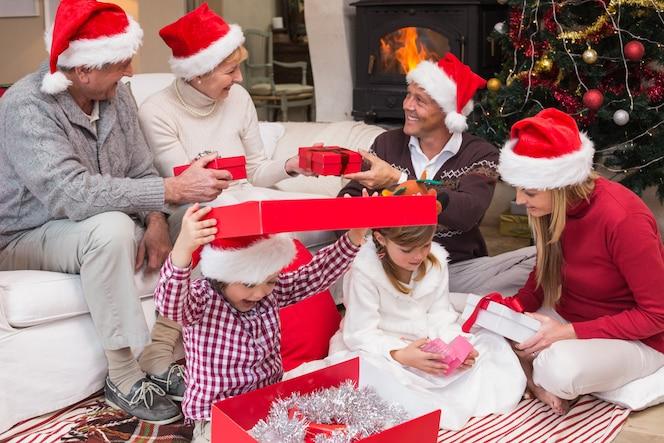 Familia feliz abriendo regalos de navidad juntos en casa en la sala de estar