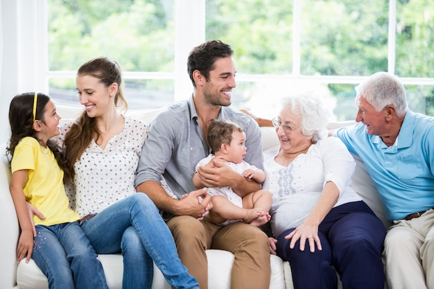 Familia feliz con los abuelos sentados en el sofá
