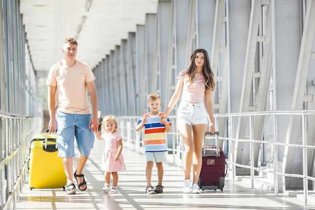 Familia feliz en el aeropuerto con maletas viajando