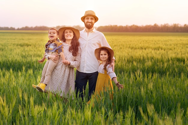 Familia feliz de agricultores, padre, madre, hijo y niña en sombrero de paja en campo de trigo al atardecer.