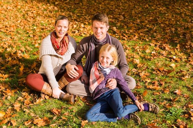 Familia feliz al aire libre sentado en el césped en otoño