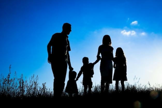 Familia feliz al aire libre en la silueta del parque