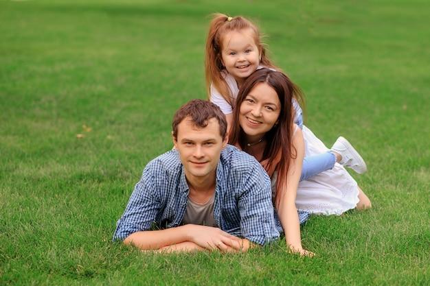 Familia feliz alegre abrazando y mirando a la cámara mientras descansa sobre la hierba verde en un día soleado en el parque