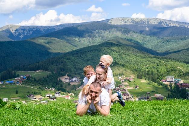 Familia feliz: alegre padre, madre y dos hijos están tumbados en la hierba verde del bosque, las montañas y el cielo con nubes.