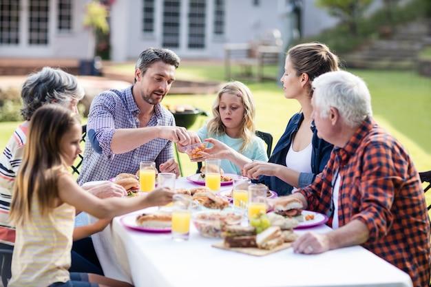 Familia feliz almorzando en el jardín