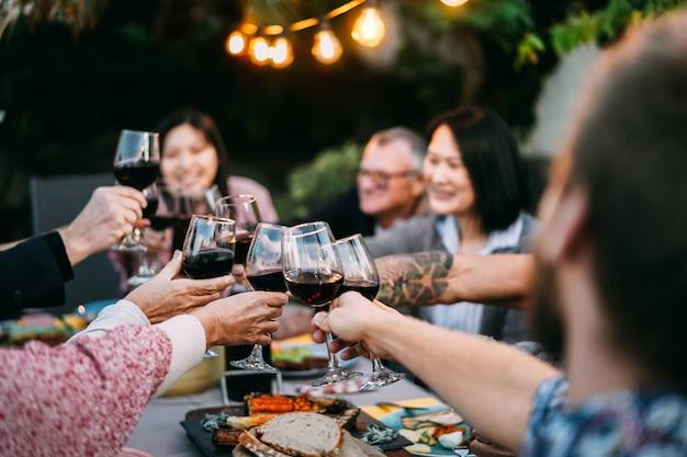 Familia feliz animando con vino tinto en la cena de barbacoa al aire libre