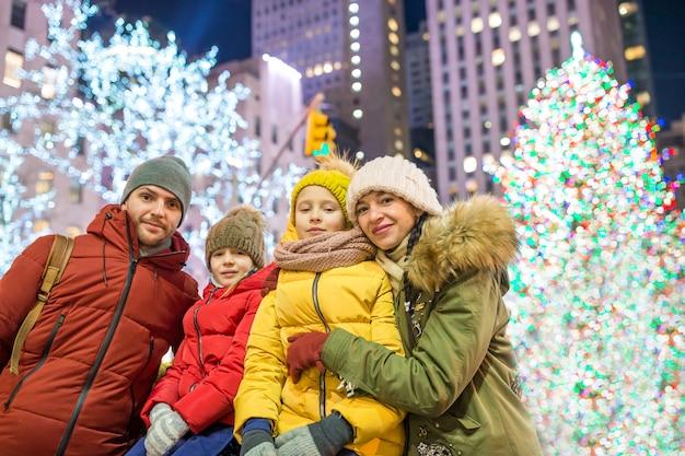 Familia feliz en el árbol de navidad rockefeller en nueva york
