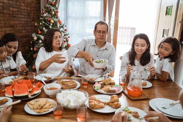 Familia feliz asiática celebrando la navidad juntos en casa