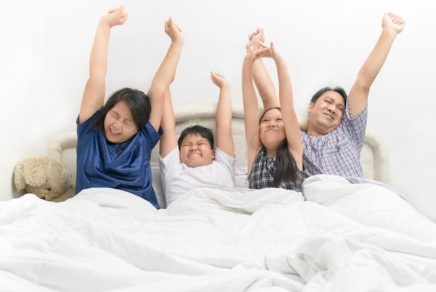 Familia feliz asiática despertando con las manos levantadas,