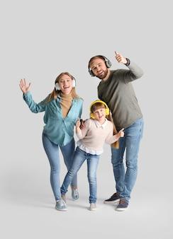 Familia feliz con auriculares en superficie clara
