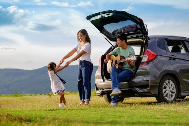Familia feliz en el auto en el campo