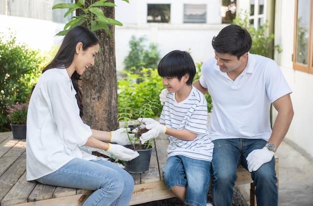 Familia feliz ayudando a plantar árboles en casa