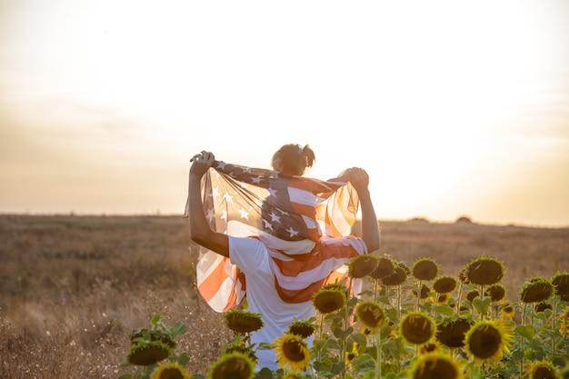 Una familia feliz con una bandera estadounidense al atardecer.